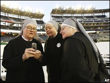Nuns look at a mobile phone before the Pope led Mass for 48,000 in a Washington stadium
