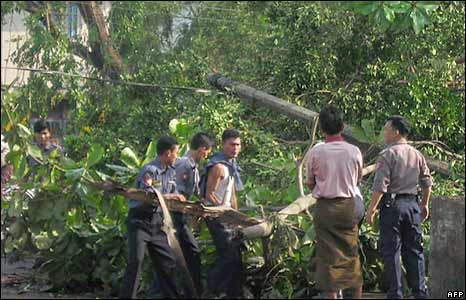 Police and residents try to clear an uprooted tree in Rangoon on 5 May 2008