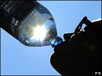 Una mujer tomando agua de una botella