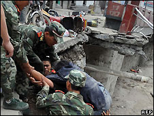 Chinese soldiers help a civilian up a collapsed road in Beichuan county, Sichuan province - 13/5/2008