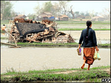 A woman walks past a house destroyed by cyclone Nargis near Rangoon, 15 May, 2008