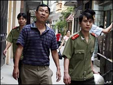 Journalist Nguyen Viet Chien is escorted away by police on 12 May 2008