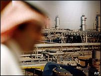 Invitado a la cumbre pasan frente a imagen de petrolera saudita.