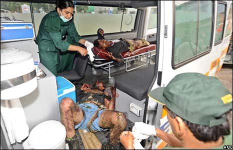 Pakistani paramedics treat injured policemen at a suicide attack site in Islamabad on 6 July, 2008.