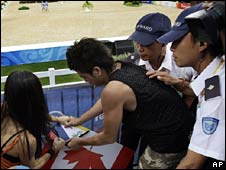 Christina Chen and another protester tries to display Tibetan flag at the equestrian event in Hong Kong