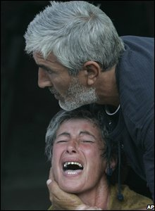 A crying Georgian woman is calmed by her husband in Gori