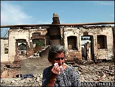 A woman walks down a destroyed main street in Tskhinvali, South Ossetia