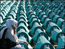 A Muslim woman grieves beside the coffins of disinterred Srebrenica victims, July 2008
