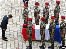 French President Nicolas Sarkozy lays a medal on the coffin of a soldier killed in Afghanistan