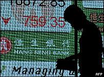 Hombre pasa frente a cartelera en Wall Street.