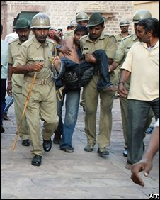 Indian police and volunteers carry injured people following a stampede at a Hindu Temple in Jodhpur on September 30, 2008