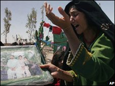 Afghan civilian holds a picture of family members allegedly killed by the US