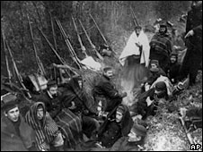 Allied troops huddle in a trench around a tiny fire near Ypres, Belgium, in 1914