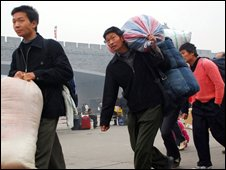 A group of Chinese migrant workers return home after they were laid off from factories in southern China's Guangdong province on Thursday