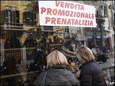 Women look at a shop window in Milan