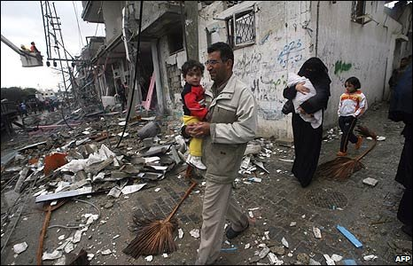 A family walk past ruined buildings in Rafah, southern Gaza