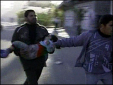 An injured boy is carried away from the school (6 January 2009)