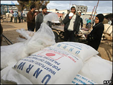 Palestinians distribute food aid received from Unwra in Rafah, southern Gaza, 8 Jan 2009