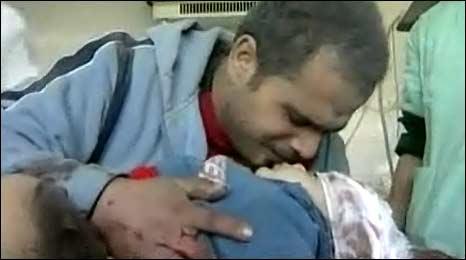 Helmi al-Samouni kisses his son Mohammed goodbye