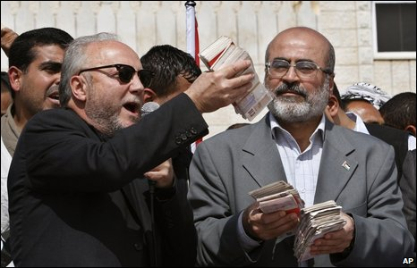 British MP George Galloway (left) donates cash to Hamas in Gaza City, 10 March 2009