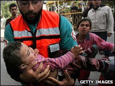 A wounded Palestinian child is carried into the Kamal Adwan hospital after an Israeli air strike on 11 January 2009