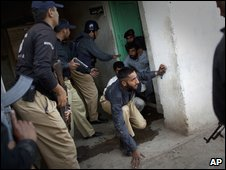 Police officers who were held hostage are freed by their colleagues inside the compound of a police training school on the outskirts of Lahore in Pakistan on Monday