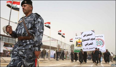 "Iraqi soldiers carry the national flag and a banner that reads in Arabic ""Parade to Mark the Iraq Pride day"" in the city of Karbala"