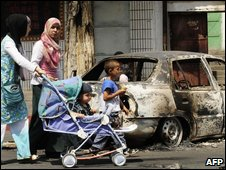 Pedestrians pass a burned out car in Urumqi, 6 July