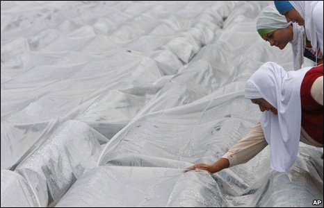 Bosniak Muslim women weep over shrouded coffins at Potocari cemetery outside Srebrenica, 11 July