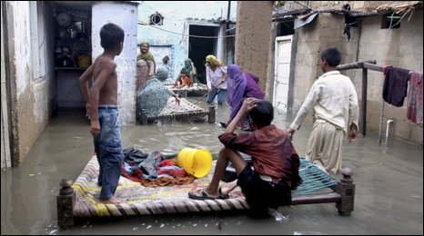 A Pakistani family in their flooded house in Karachi, July 19