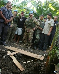 UN peacekeepers inspect the site where rockets were fired from Lebanon