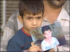 A cousin holds a photo of Muntadar