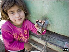 A girl stands next to a water tank near Nablus, West Bank. Photo: October 2009