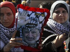 A Palestinian woman holds a picture of Yasser Arafat in Ramallah on 11 November 2009