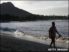 A man walks along Waikiki beach, Honolulu, Hawaii
