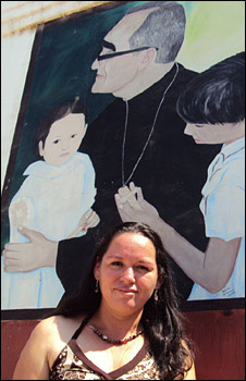 Irma in front of a mural depicting the photograph of her and her  cousing with Archbishop Romero