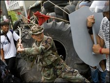 Khattiya Sawasdipol tests a red-shirt's home-made shield in  Bangkok, 11 May