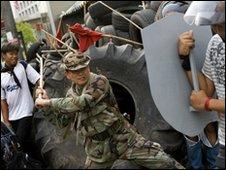 Khattiya Sawasdipol tests a red-shirt's home-made shield in  Bangkok, 11 May