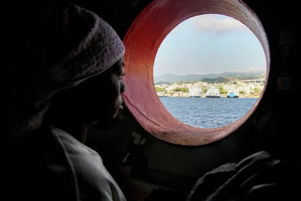 FILE - In this Saturday June 25, 2016 file photo, a woman looks out of the porthole from aboard the 'Aquarius' rescue vessel after arriving in Sicily, Italy with more than 600 migrants aboard the ship rescued by SOS Mediterranee and the medical aid group Medecins Sans Frontieres (MSF). By trying to prevent migrants from taking the dangerous sea journey across the Mediterranean, they are dooming them to prolonged abuse in Libya at the hands of authorities and the country's many militias, rights groups warn. (AP Photo/Bram Janssen, File)