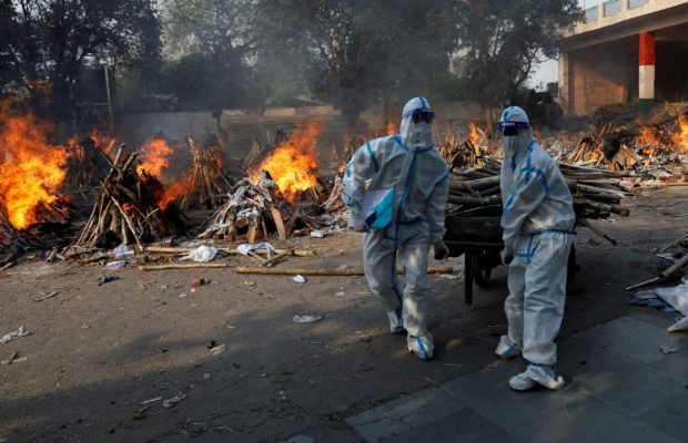 Health workers wearing personal protective equipment (PPE) carry wood to prepare a funeral pyre for a coronavirus disease (COVID-19) victim during a mass cremation at a crematorium in New Delhi, India, April 26, 2021. REUTERS/Adnan Abidi