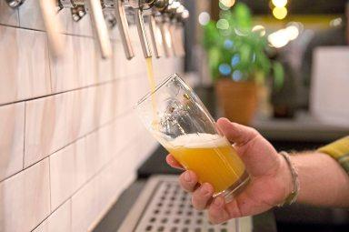 "Ian Warner, taproom manager, pours a glass of Dancing Gnome Beer's double IPA ""Orbital Convoy"". (Antonella Crescimbeni/Post-Gazette)"