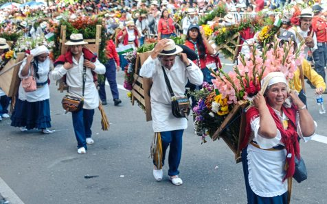 "Flower farmers carry elaborate flower arrangements on wooden ""silletas"" Monday Aug. 7, 2017, during the 60th anniversary of the flower festival in Medellin, Colombia. (Nate Guidry/Post-Gazette)"