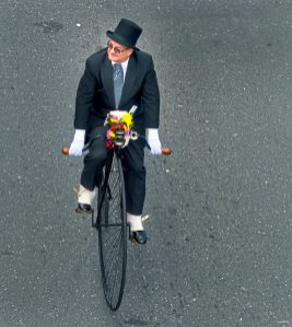 A man dressed in a tuxedo and top hat makes his way down the parade route on a high wheeler bicycle Monday Aug. 7, 2017, during the 60th anniversary of the flower festival in Medellin, Colombia. (Nate Guidry/Post-Gazette)