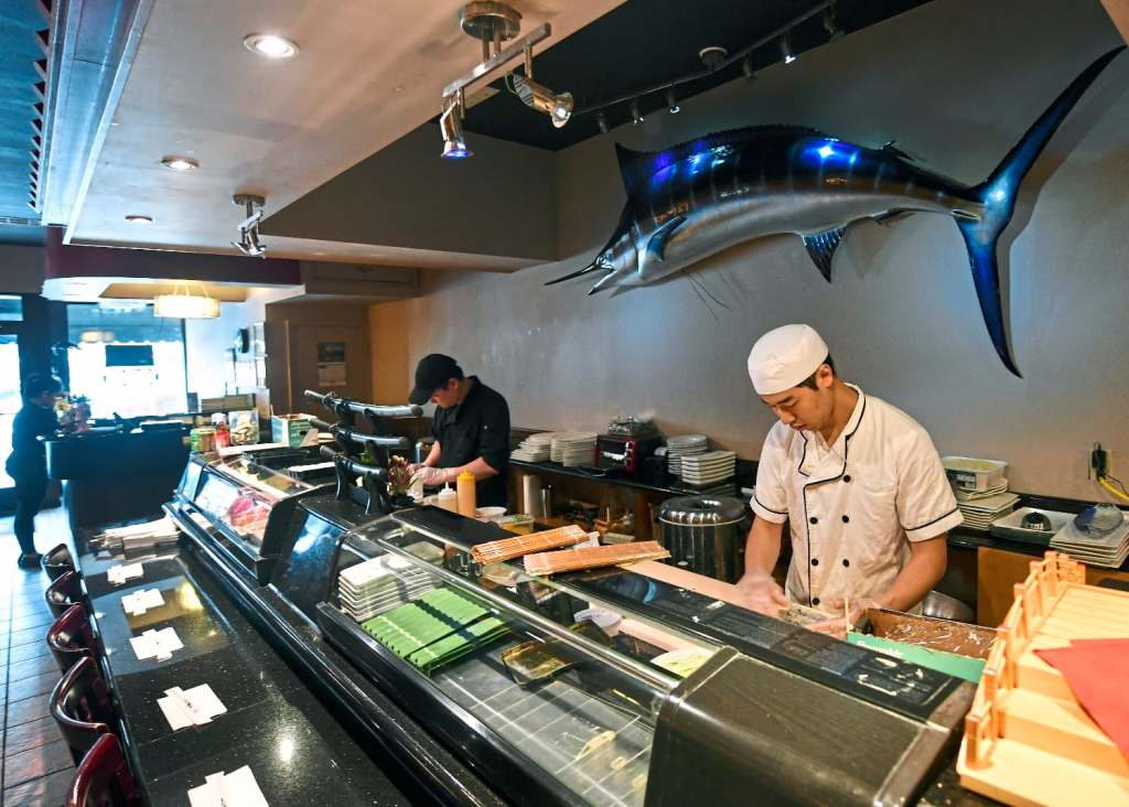Chefs J.J. Wang, left, and Zhang Ray prepare lunchtime meals at Yama restaurant in Beaver. (Nate Guidry/Post-Gazette)
