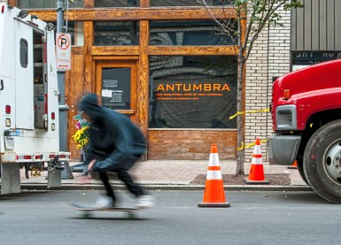 """A skateboarder rides past the 707 Penn Gallery on Wednesday, Oct. 24 , 2018, in Downtown. The gallery is currently housing Pittsburgh artist Keny Marshall's exhibition """"Antumbra"""". (Andrew Stein/Post-Gazette)"""