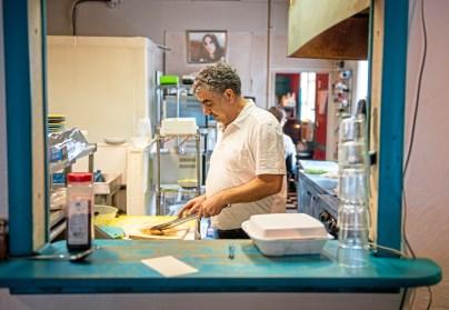 Owner Raja Khalil cuts chicken in the kitchen of Kabob-G Grill in Castle Shannon. (Andrew Stein/Post-Gazette)