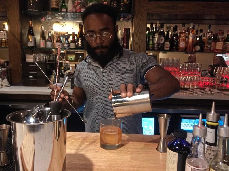 Alec El, beverage director at Yuzu Kitchen, pours his Shochu Old Fashioned at the Downtown restaurant. (Bob Batz Jr./Post-Gazette)