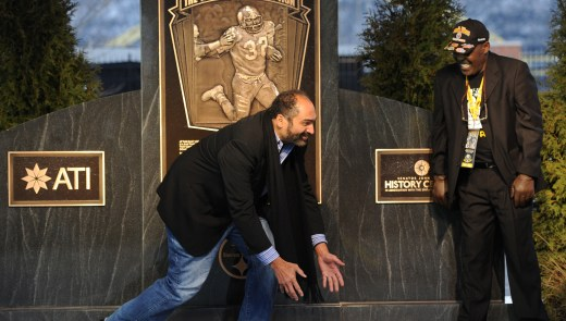 Franco Harris demonstrates the Immaculate Reception as John Frenchy Fuqua looks on at the unveiling of a historical marker designating the spot where the the play occurred on the North Side on Saturday, December 22, 2012. (Rebecca Droke/Post-Gazette)
