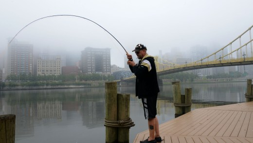 "Russ Stratton , of the North Side, gets a ""bite"" while fishing in the Allegheny River , on the North Shore. (Darrell Sapp / Post-Gazette)"