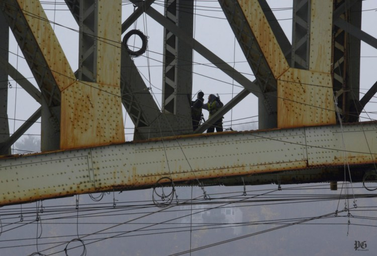 Workers under the decking of the Liberty Bridge pulls in another coil of cable.  Darrell Sapp/Post-Gazette